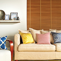 Photo of wooden blinds behind yellow sofa in living room